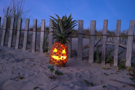Jack o lantern made out of pinapple glowing at dark on beach photo