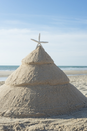 Christmas tree on beach made out of sand with starfish as top decoration. Concept for escaping the cold tropical xmas photo