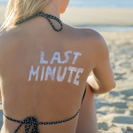 Last Minute written with sunscreen on back of attractive woman sitting on beach looking at ocean Stock Photo