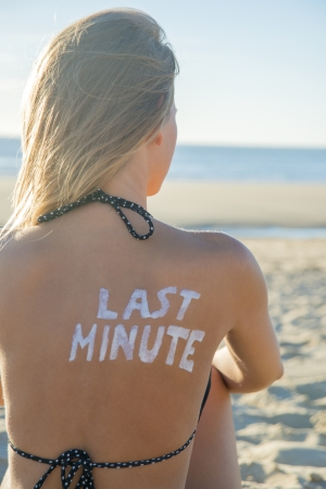 Last Minute written with sunscreen on back of attractive woman sitting on beach looking at ocean photo