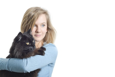 Friendship between animal and human: woman holding black tomcat pet in her arms Stock Photo