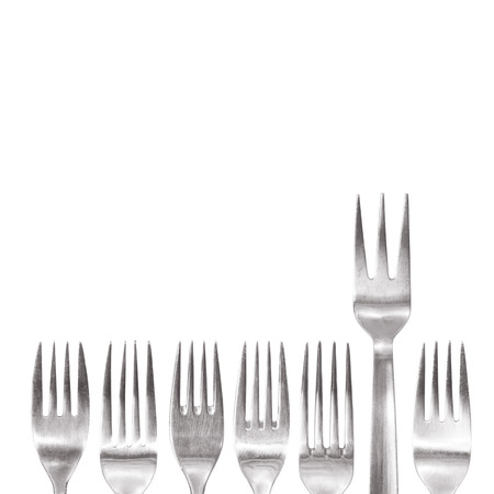 special individual: individual fork with three spikes standing out of the crowd of different shaped normal cutlery. special restaurant concept Stock Photo