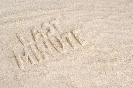 Last minute written in sand on beach. holiday theme background concept Imagens