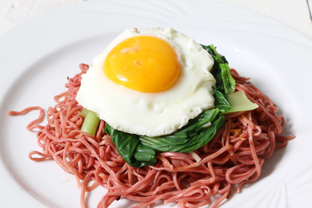 Beetroot instant noodle with vegetable and  fried egg topping