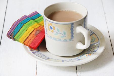 Pastel de capas de colores o Kek Batik Sarawak servido con una taza de té con leche