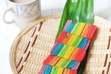 Pastel de colores pastel o Kek Batik Sarawak en una bandeja de bambú Foto de archivo