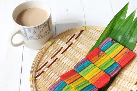 Bolo de camada colorida ou Kek Batik Sarawak servido com uma xícara de chá