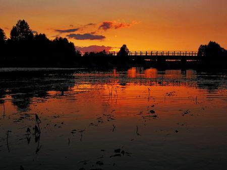 bridge through river illuminate red sunset rays  photo