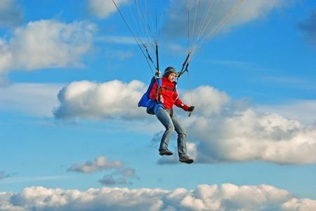 operates: Giovane ragazza paracadutista in cielo nuvoloso opera un paracadute