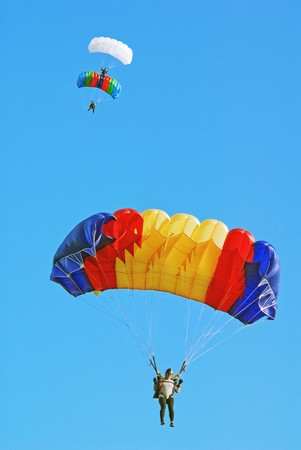 parachutists: Parachutists under multi-coloured parachutes in the blue sky Stock Photo