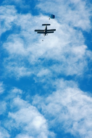 parachutists: Jump of parachutists from the plane against the blue sky with clouds Stock Photo