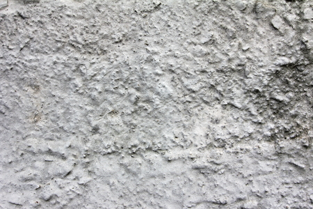 Eroded old grey concrete at a wall for dirty scratched texture, background