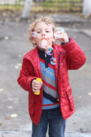 A little curly cheerful boy in a bright red jacket walks on the street in the fall and blowing soap bubbles