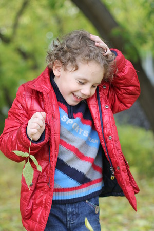 little curly cheerful boy walks in the forest among the trees and fallen yellow leaves in autumn