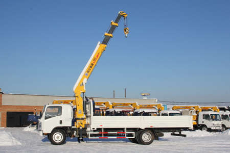 Great white auto truck crane standing on a construction site in winter - Russia, Crimea -January, 21, 2016