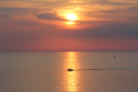 silhouettes of boats, yachts, ship on the background of yellow - orange sky at sea at sunset or sunrise, The beautiful nature of black sea Stock Photo