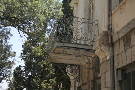 a old balcony with wrought iron railings twisted on the dilapidated wall closeup