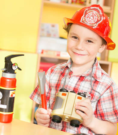 portrait of a cheerful smiling boy playing with toys and binoculars in his hands in a fire suit as a firefighter