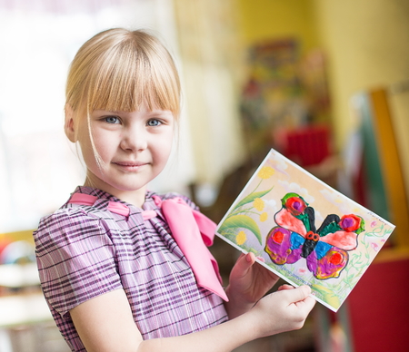 portrait of a cheerful smiling girl holding a bright colorful picture of butterfly painted colors, plasticine and crayons in kindergarten - Moscow, Russia - February 4, 2016 Editorial