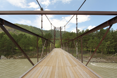 a wooden bridge over the river on a background of blue sky