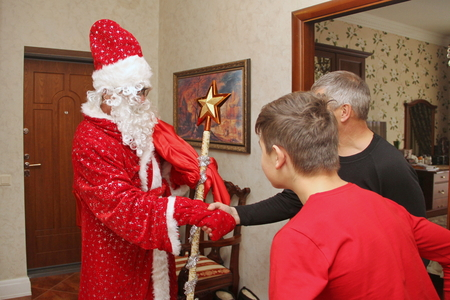 Santa Claus carrying a bag of gifts and his staff with the big gold star went to the apartment and greets a man and a boy - Russia, Moscow, 07 December, 2016 Editorial