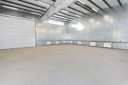 Lege lichte parkeergarage, magazijn interieur met grote witte poorten en ramen binnen