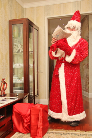 Santa Claus reading a letter in a long bright suit in the room next to a big red bag with gifts, not posing, natural photo - Russia, Moscow, 07 December, 2016 Editorial