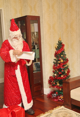 meet and greet: Santa Claus reading a letter in a long bright suit in the room next to a big red bag with gifts and beautiful dressed christmas tree, not posing, natural photo - Russia, Moscow, 07 December, 2016