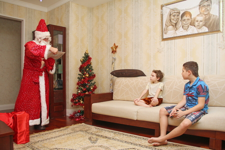 Santa Claus came to children home, reading a letter in a long bright suit in the room next to a big red bag with gifts and beautiful dressed christmas tree, not posing, natural photo - Russia, Moscow, 07 December, 2016
