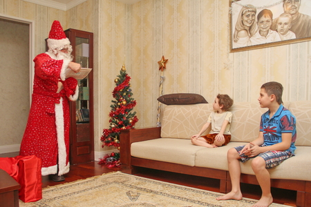 Santa Claus came to children home, reading a letter in a long bright suit in the room next to a big red bag with gifts and beautiful dressed christmas tree, Boys listening and gifts waiting, not posing, natural photo - Russia, Moscow, 07 December, 2016 Editorial