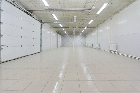 empty light parking garage, warehouse interior with large white gates and gray tile floor Stock Photo