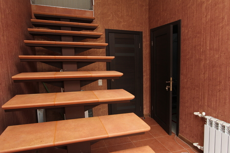 An Open staircase with stone steps going up to the inside corridor rooms close-up on a background of bright walls and dark doors