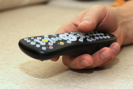 A TV remote controller in the mans hand on light textile background with empty copy-space