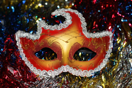 a bright red - gold mask on the background of multi-colored Christmas-tree tinsel