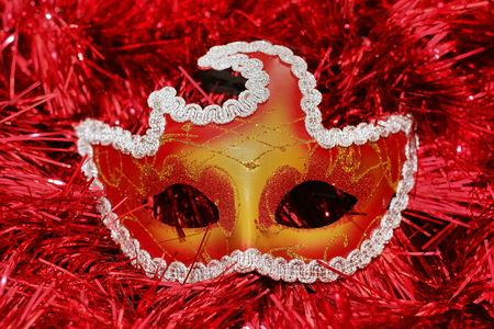 a bright colored mask on a red background Christmas-tree tinsel Stock Photo