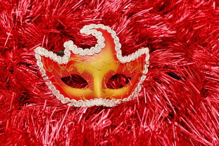a bright colored mask on a red background Christmas-tree tinsel with free copy space