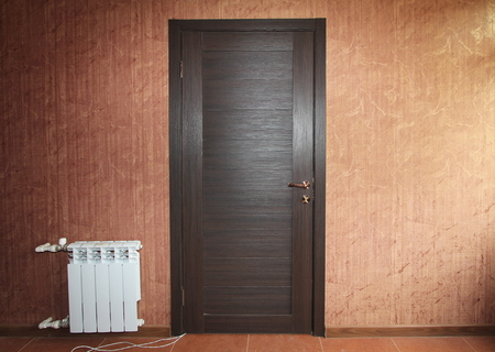 a dark wooden closed door close-up on the wall with red vintage wallpaper and white battery radiator Stock Photo