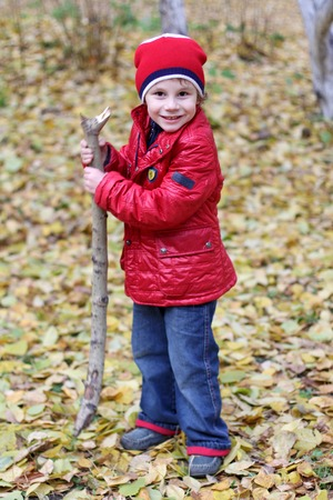 Portrait of a happy joyful child in a hat and a red jacket, jeans against a background of autumn forest and yellow leaves