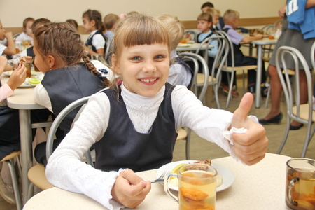 merry schoolgirl Sitting At Table In School Cafeteria Eating Meal. drinking juice and shows thumbs up - Russia, Moscow, the first High School, the first class b - September 30 2017 Editorial