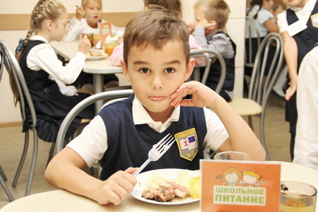 merry schoolboy Sitting At Table In School Cafeteria Eating Meal. drinking juice - Russia, Moscow, the first High School, the first class b - September 30 2017