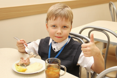merry schoolboy Sitting At Table In School Cafeteria Eating Meal. drinking juice and shows thumbs up - Russia, Moscow, the first High School, the first class b - September 30 2017