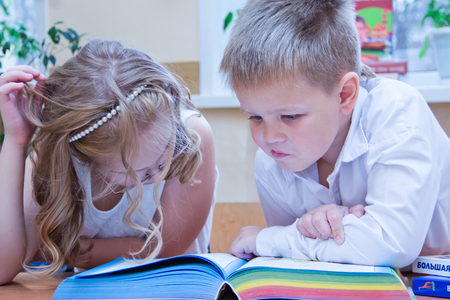 Two small schoolchildren, boy and girl sitting together at the desk in classroom, reading the study book - Russia, Moscow, first high school, 2 class b - October 28, 2017