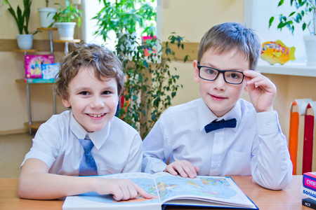 Two small schoolboys, sitting together at table in class, reading the study book, looking at camera - Russia, Moscow, first high school, 2 class b - October 28, 2017