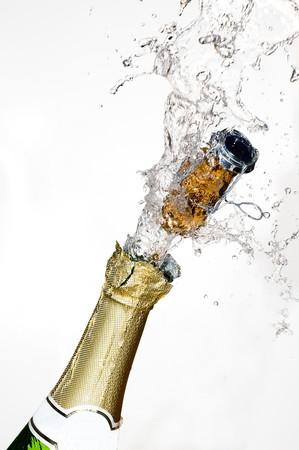 brindisi champagne: Close-up di esplosione bottiglia di champagne sughero con sfondo bianco