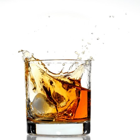 whiskey glass: Whiskey splash studio isolated on white background