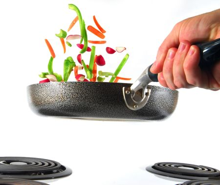 Flipping veggies with pan studio isolated on white background photo