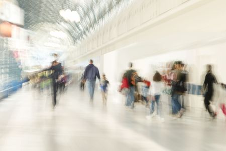 People are rushing in shopping centre. A zoom lens was used to make the people appear blurry.