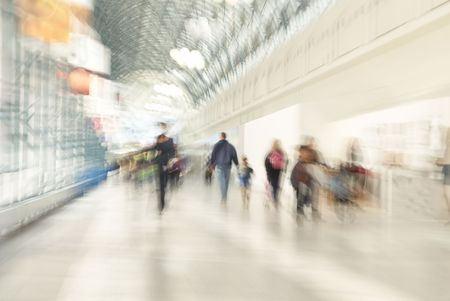 rush: People are rushing in shopping centre. A zoom lens was used to make the people appear blurry.