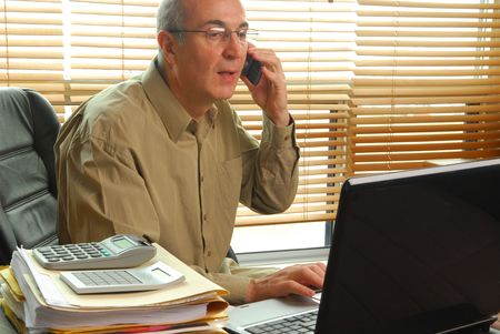 Businessman working with laptop and calling by cell phone Stock Photo - 4839072