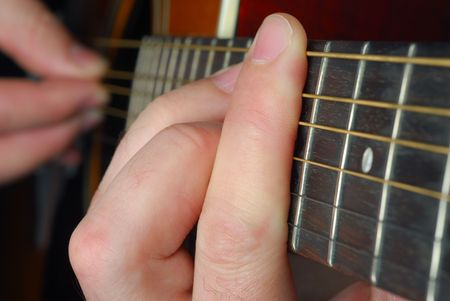 frets: Musician is playing guitar in low light situation
